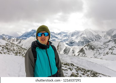 portrait male mountaineer in snowy mountains, with a backpack