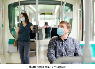 Portrait of male passenger in disposable face mask and latex gloves traveling by city streetcar. Concept of prevention and social distancing in coronavirus pandemic