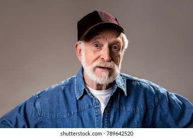 Portrait of male pensioner standing and looking at camera in inquiring manner. Isolated on grey background