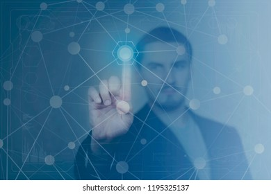 Portrait of male person touching with finger hexagonal button on digital dashboard. Interface touchscreen and technology concept. Blue abstract background