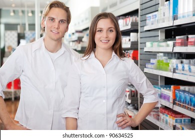 Portrait of male pharmacist technician standing with female colleague
