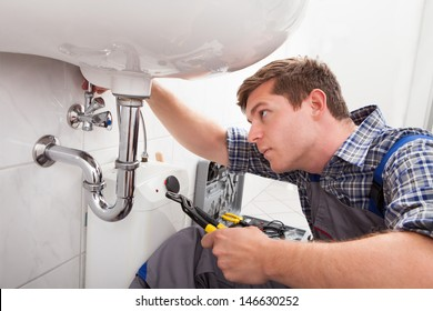 Portrait of male plumber fixing a sink in bathroom