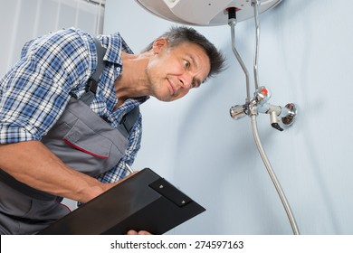 Portrait Of Male Plumber Holding Clipboard Looking At Electric Boiler