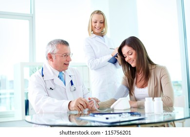 Portrait of male practitioner measuring blood pressure of patient with nurse near by