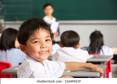 Portrait Of Male Pupil Working At Desk In Chinese School Classroom