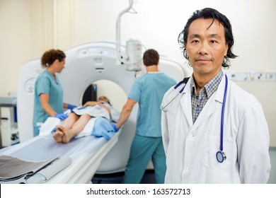 Portrait of male radiologist with nurses preparing patient for CT scan test in hospital