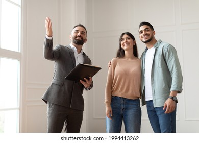 Portrait Of Male Realtor Or Architect Wearing Suit Showing New Empty House To Smiling Millennial Buyers, Pointing. Husband Embracing His Wife, Visiting Residential Building, Choosing Home For Family