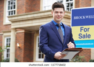 Portrait Of Male Realtor Standing Outside Residential Property With For Sale Sign