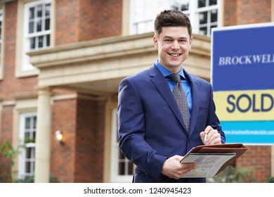 Portrait Of Male Realtor Standing Outside Residential Property With Sold Sign