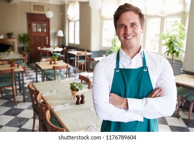 Portrait Of Male Restaurant Manager In Empty Dining Room