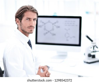 Portrait of a male scientist with a monitor looking at the camer