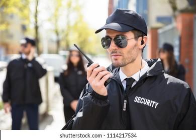 Portrait Of A Male Security Guard Talking On Walkie Talkie