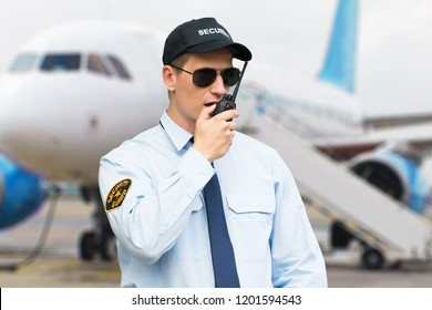 Portrait Of A Male Security Guard Talking On Walkie Talkie At An Airport