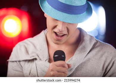 Portrait of male singer wearing blue hat. handsome man singing into microphone alone