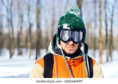 Portrait of male skier in the forest, winter, green cap