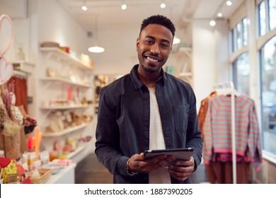 Portrait D'Un Propriétaire De Petites Entreprises Masculin Vérifie Le Stock En Achetant Une Tablette Numérique