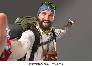 Portrait of a male smiling fully equipped tourist with backpack and the camera on gray background