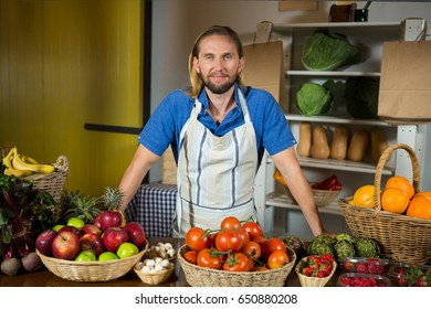 Portrait of male staff standing near vegetable counter at organic section in market