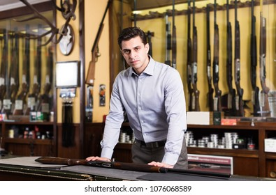 Portrait of male standing near showcase with rifles in hunting shop