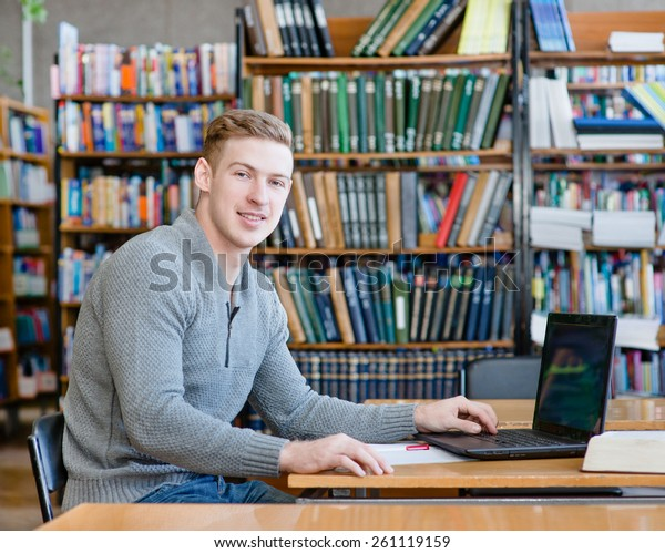 Portrait male student with laptop in the university library