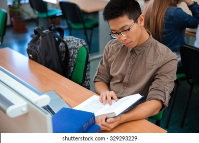 Portrait of a male student reading book in classroom