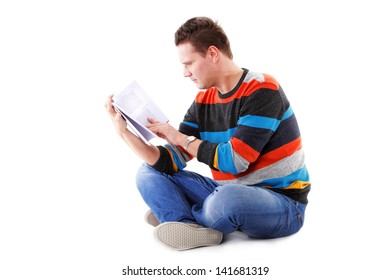 Portrait of a male student sitting reading a book isolated on white