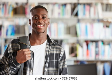 Portrait Of Male Student Standing In College Library