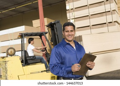 Portrait of a male supervisor with clipboard and forklift truck driver in the background