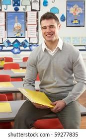 Portrait Of Male Teacher Sitting At Desk In Classroom