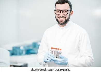 Portrait of a male technician standing with test tubes in the laboratory