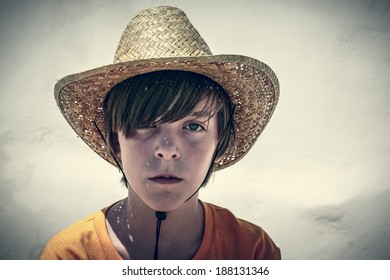 portrait of a male teenager with straw hat, vintage color filer.