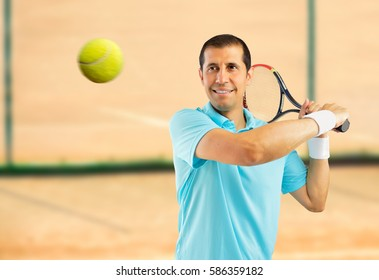 portrait of a male tennis player swatting the ball on a clay court