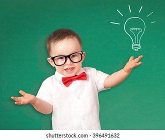 Portrait of male toddler with lightbulb picture on chalkboard