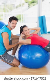 Portrait of a male trainer helping woman with her exercises at a bright gym