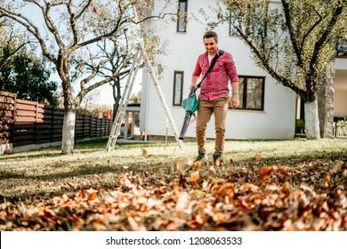 Portrait of male using garden blower, home gardening details