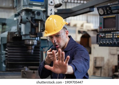 Portrait of male worker talking on radio phone calling team worker. machine technology invention industry manufacturing factory