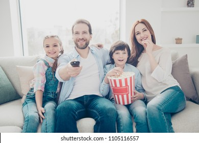 Portrait of mama daddy two kids looking tv sitting on sofa having pop-corn in hands using remote-control searching interesting cartoons enjoying cinema indoor. Weekend holiday free time concept
