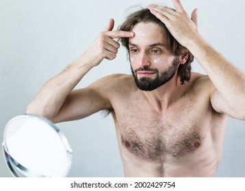 Portrait of man applying moisturizer to face.Young fine-looking man skincare beauty portrait isolated in studio.