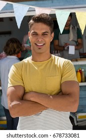 Portrait of man with arms crossed standing by food truck