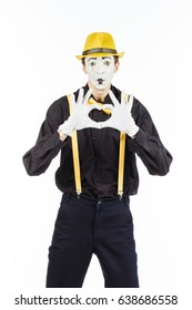 Portrait of a man, artist,clown, MIME. Shows a heart isolated on white background in Studio.