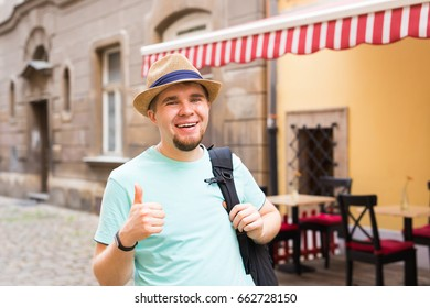 Portrait of a man with backpack giving thumb up in the city