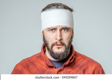 Portrait of man with bandages wrapped around his head isolated on gray background