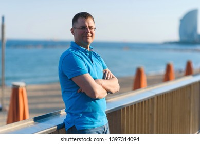 portrait of man at beach fence at sunset