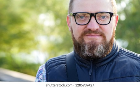 Portrait of a man with a beard with glasses. Close up male face.