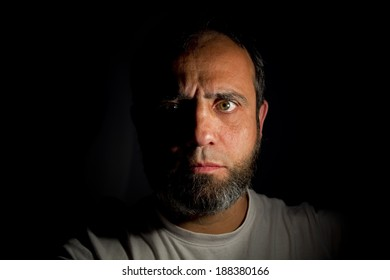 Portrait of a man with a beard middle aged and dark background