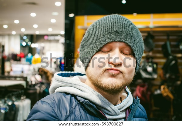 Portrait of a man with a beard with a mustache, putting on winter spring knitted hats in the store, with an emotional face shopping