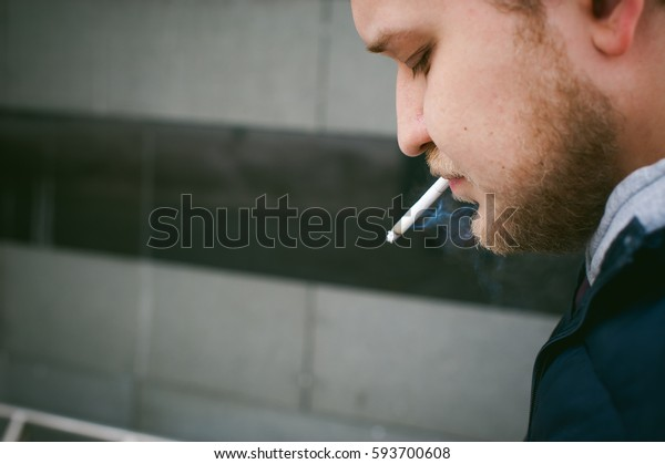 Portrait of a man with a beard with a mustache, smoking a cigarette, with an emotional face in the open air