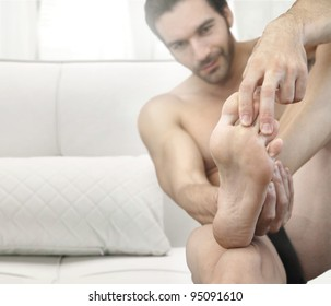 Portrait of a man in bed looking at his feet with focus on the foot