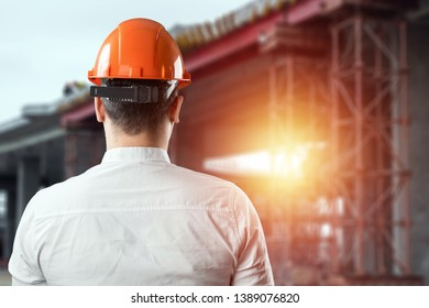 Portrait of a man from behind in a construction, orange helmet against the background of a construction site. Concept architecture, construction, engineering, design, repair. Copy space