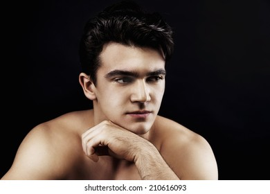 Portrait of a man with black hair on a black background